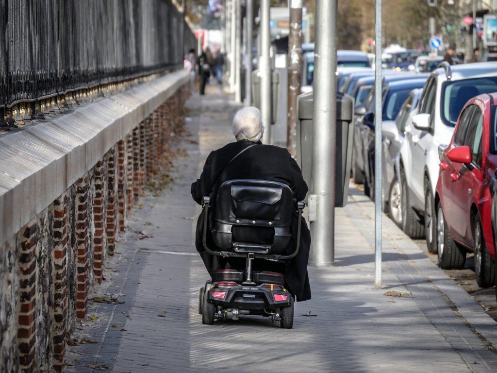 ältere Frau, die im Rollstuhl spazieren geht