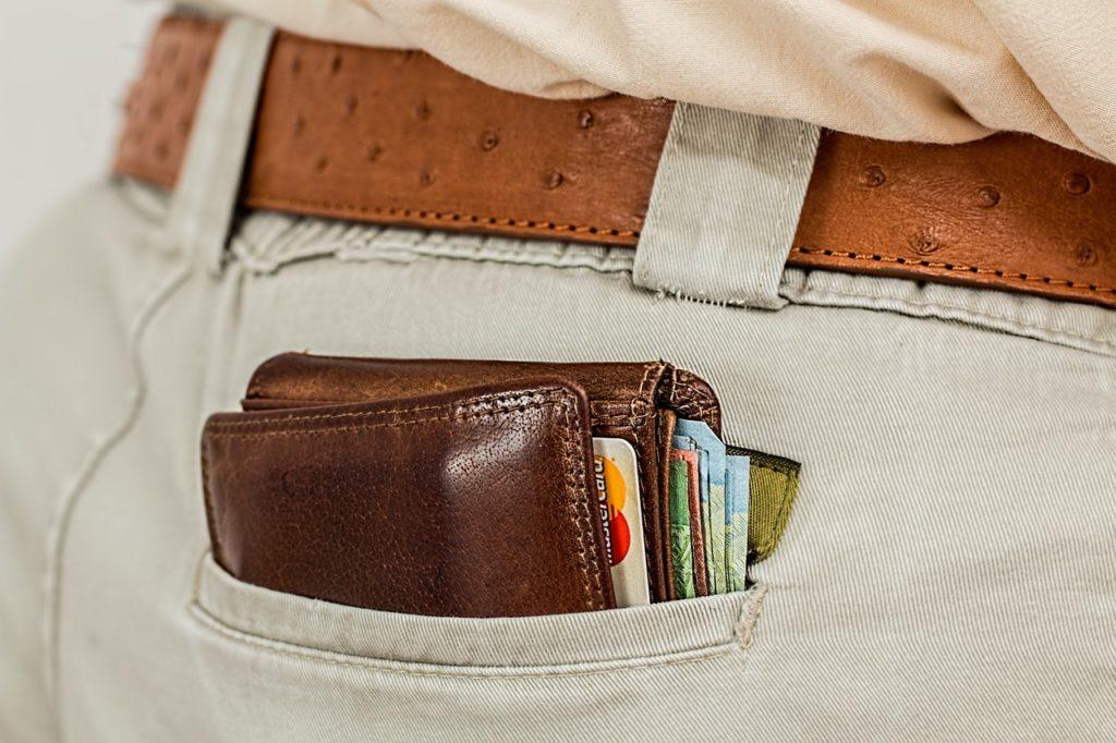eine Person, die eine Brieftasche in der Hintertasche hält